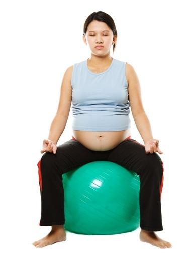 Mulher grávida praticando relaxamento de yoga