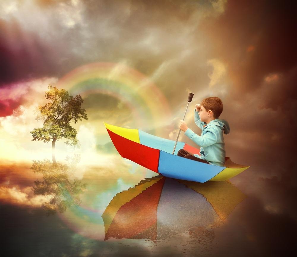Criança sentada em um guarda-chuva como um barco, olhando para uma árvore com arco-iris atrás - foto: Angela Waye/ShutterStock.com