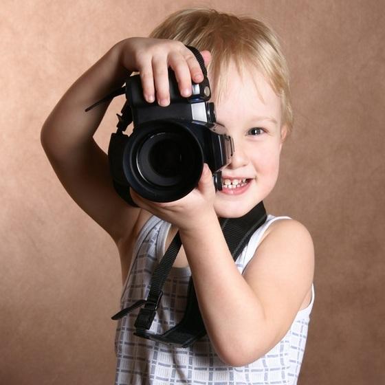 Criança segurando máquina fotográfica - Loskutnikov / ShutterStock